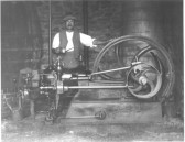 DBR337 Unknown man (possibly Mr Jacobs) with engine used to power a mangel and chaff cutter in barn - photo attributed to William Vaux